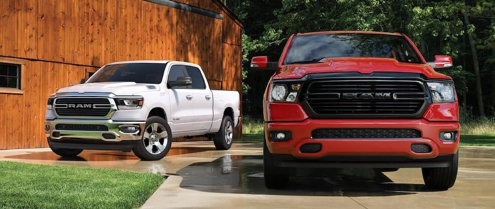 Two 2020 RAM 1500 models parked in front of a barn