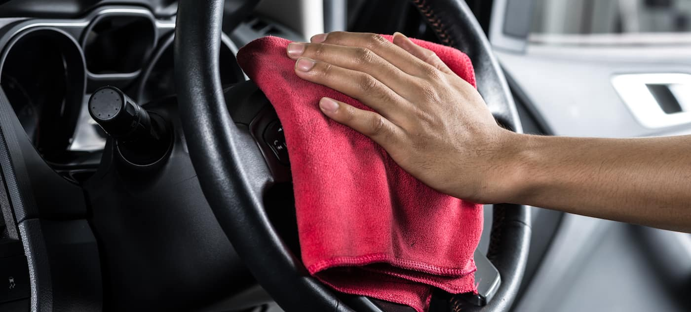 A man sanitizing the inside of a car
