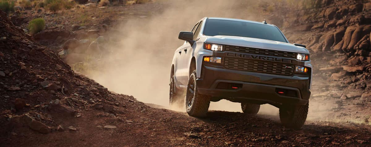 The Chevy Silverado Trail Boss is a powerful, off-roading truck that stands out in its already niche market. It is a unique model in a unique field. While many people think that all trucks are good choices for off-roading, they aren't. The Silverado Trail Boss is designed specifically for this rugged terrain and for the unpredictable conditions that you can face.  Because the Chevy Silverado Trail Boss is so well constructed that it continues to deliver reliable performance year after year, making it one of many Chevy models that is a good investment previously owned. You can shop previously owned models of the Silverado Trail Boss to save money and get more flexibility in your options, or you can shop the latest model to get the best in mechanical options and technology. Here's a look at what you can expect to find when you shop for the Chevy Silverado Trail Boss:  Off-Road Specs The Chevy Silverado Trail Boss is outfitted with features that make it easier for the truck to handle the toughest of terrains. Some features that you'll find on the Trail Boss include larger and wider tires with deeper tread, upgraded suspension systems that can better handle all the bumps along the road and cushion the ride, hill descent control, an automatic locking rear differential, and more. The truck is designed to help you handle everything you might encounter on the road.  Performance You likely aren't going to drive very fast when you're off-roading, unless you're just out in some flat terrain. However, you do need a lot of power for off-roading, and the Chevy Silverado Trail Boss has it in spades. The specifics depend upon what model year you buy and what powertrain was included with it. What you will find is, typically, a V8 engine that has plenty of horsepower, but even more torque, which is what you need to pull yourself out of and through tough terrain. It also helps you to haul heavy loads.  Convenience Features There are a few trim levels available for the Chevy Silverado 