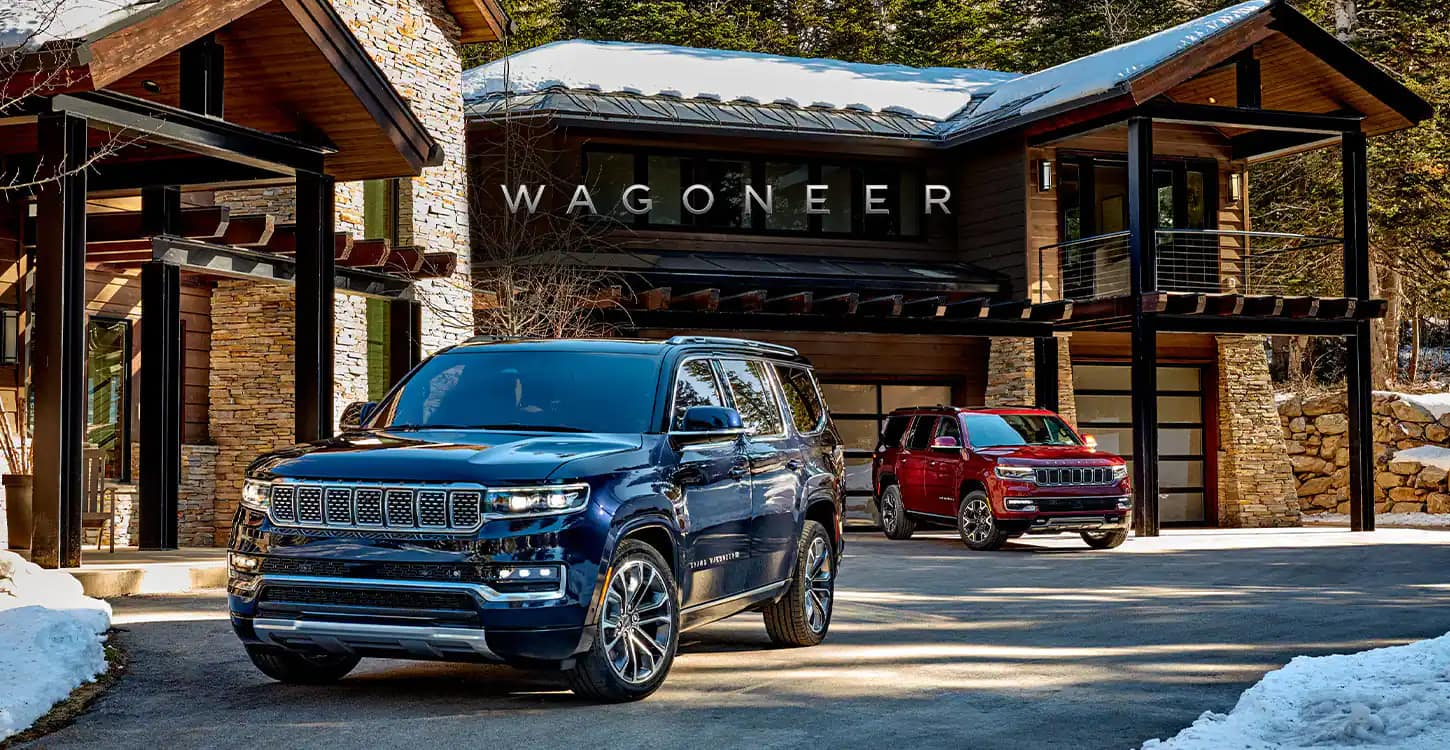 Wagoneer. The 2022 Wagoneer and 2022 Grand Wagoneer parked in the driveway of a large chalet.
