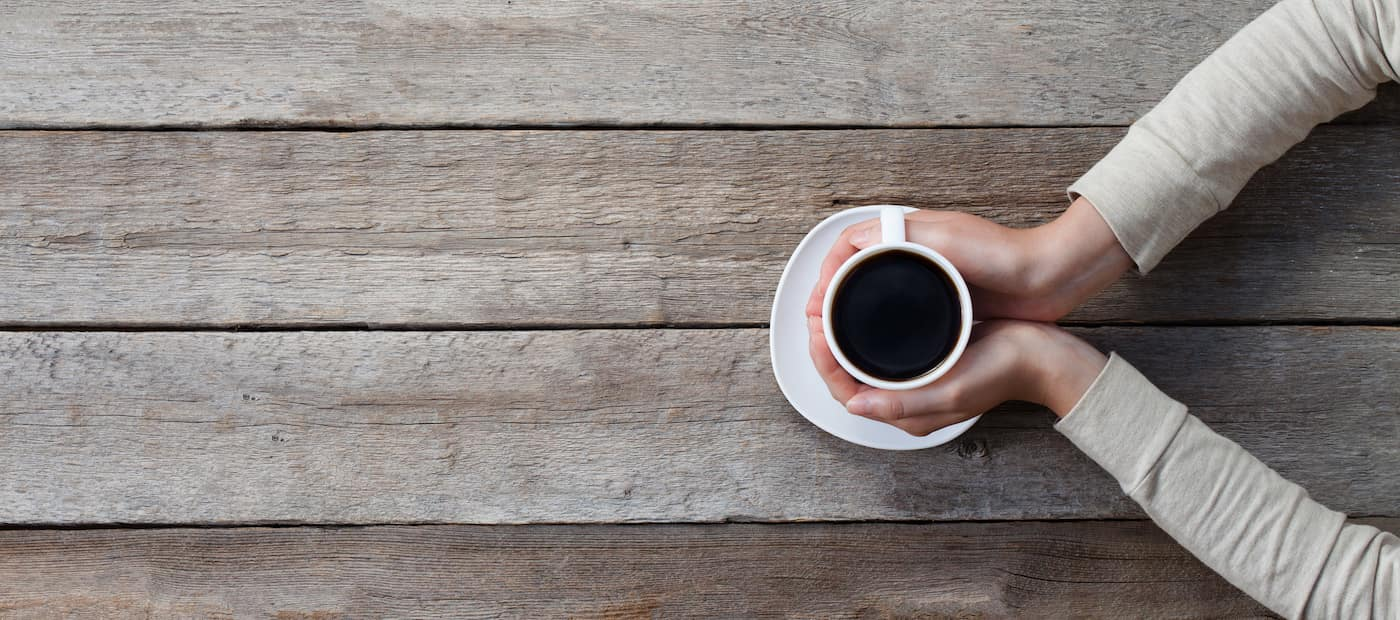 woman hands holding mug of hot coffe cup that standing on wooden table