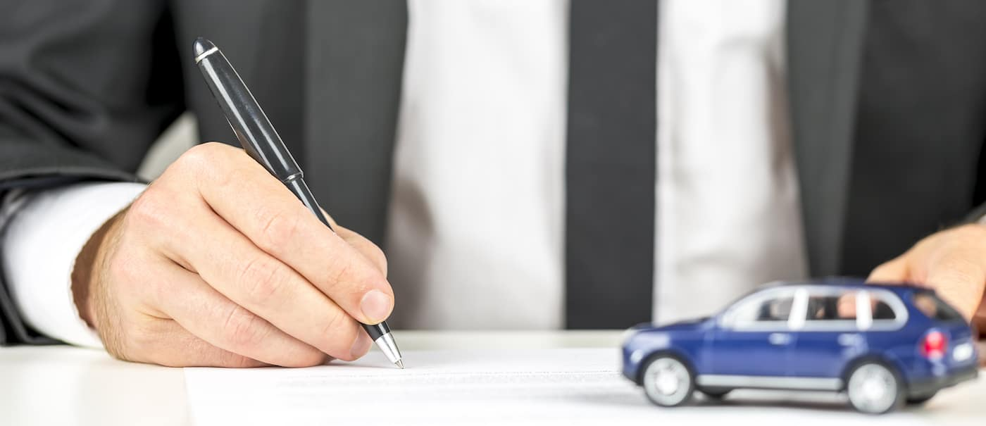 Closeup of man signing a contract of car sale.