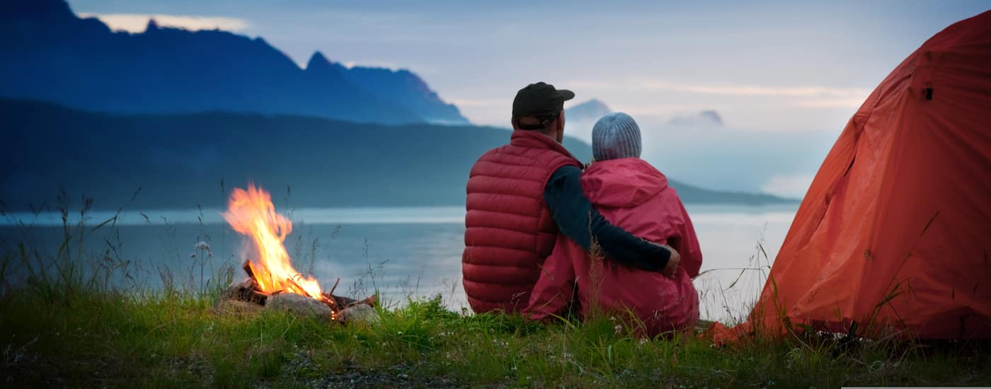Couple sitting in front of a campfire with mountains in the background