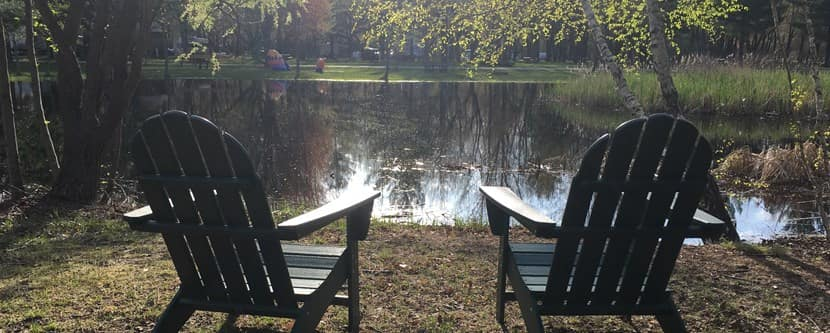 Two lawn chairs facing a lake