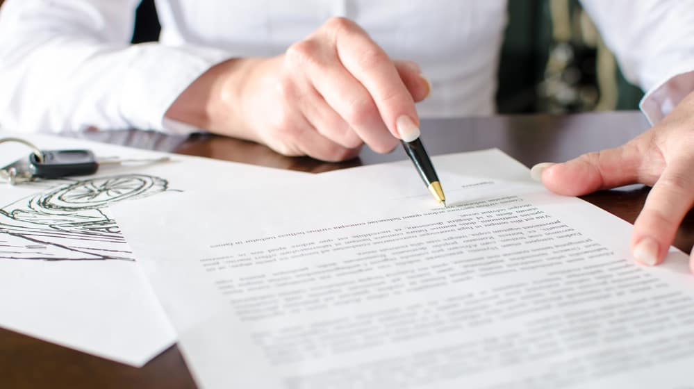 Woman's hand with pen scanning an auto financing contract.