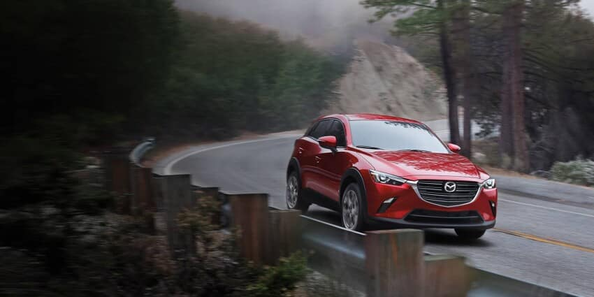 Red 2020 Mazda CX-3 turning along a curve on a mountain road