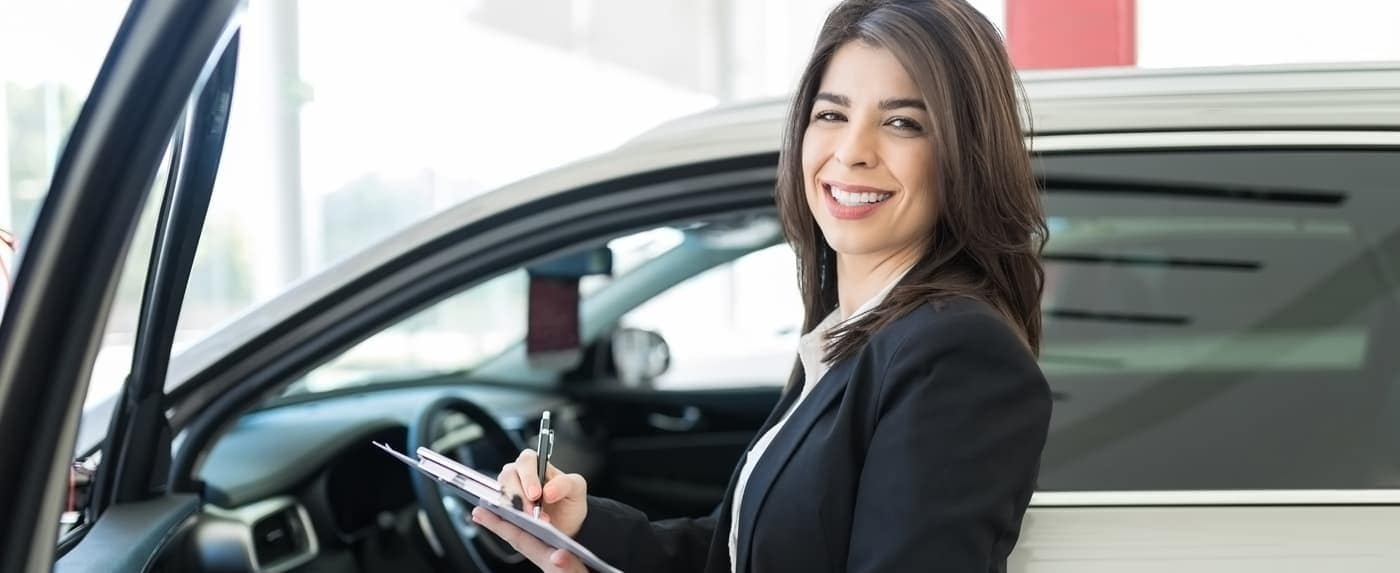 Saleswoman with car and clipboard