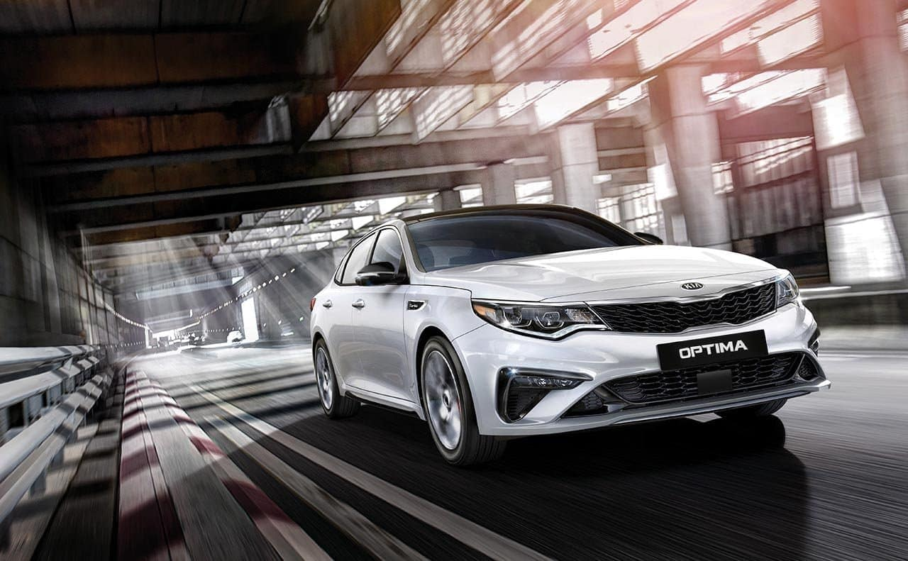 2019 Kia Optima in white driving down the road