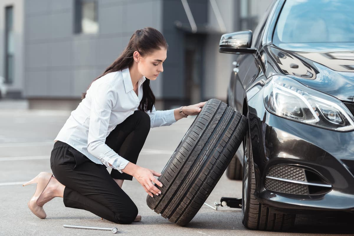 Woman replacing tire on car