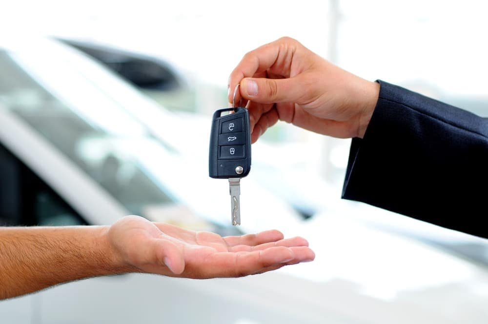 Car sale salesman passing key to consumer