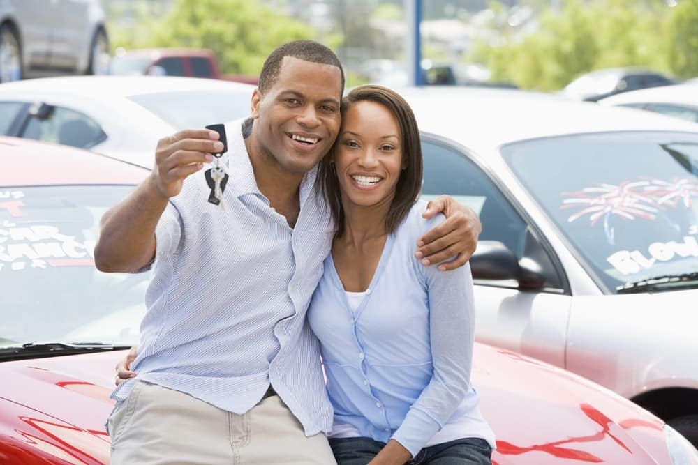Couple holding up car keys of new car