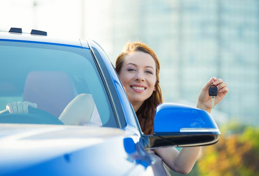 Woman holding up car keys in new car