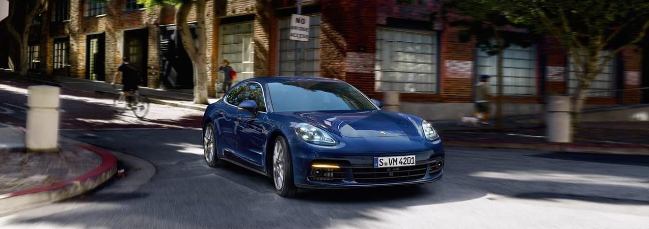 Blue Porsche Panamera driving on a town road