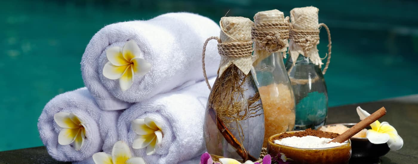 Spa towels and salts in front of a blue water background