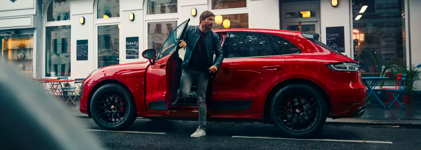 2020 red porsche macan man stepping out of model