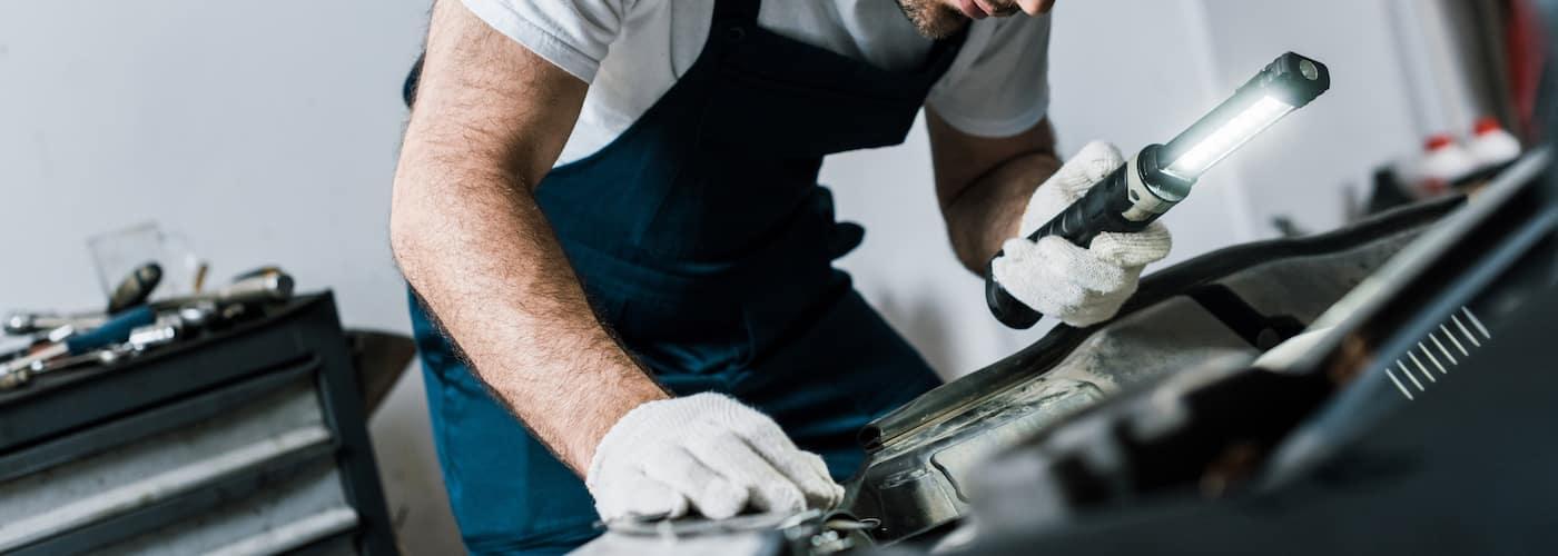 mechanic checking under hood of car with flashlight closeup