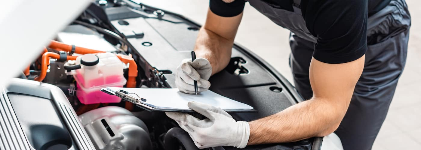 mechanic checking under hood of car close up with maintenance clip board