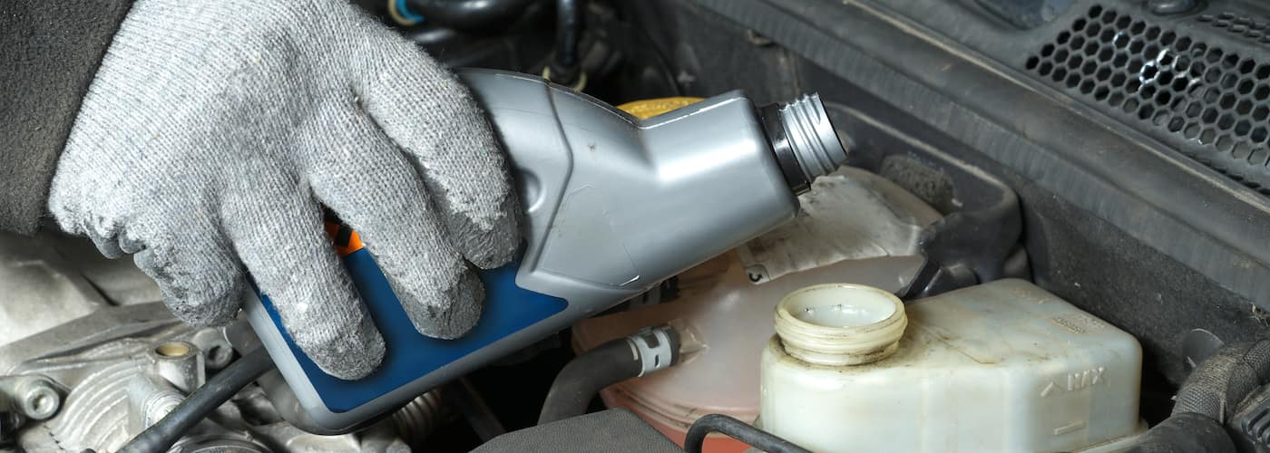mechanic gloved hand topping off brake fluid close up