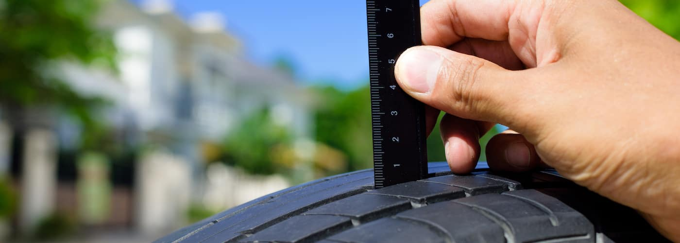 checking tire tread with ruler