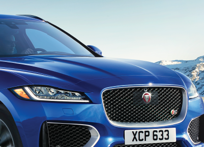 CLOSE UP IMAGE OF FRONT RIGHT PASSENGER SIDE OF A 2020 BLUE JAGUAR F-PACE.