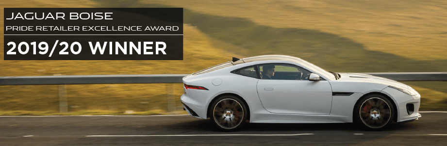 JAGUAR BOISE. PRIDE RETAILER EXCELLENCE AWARD. 2019/20 WINNER. WHITE JAGUAR F-TYPE DRIVING DOWN ROAD IN COUNTRYSIDE.