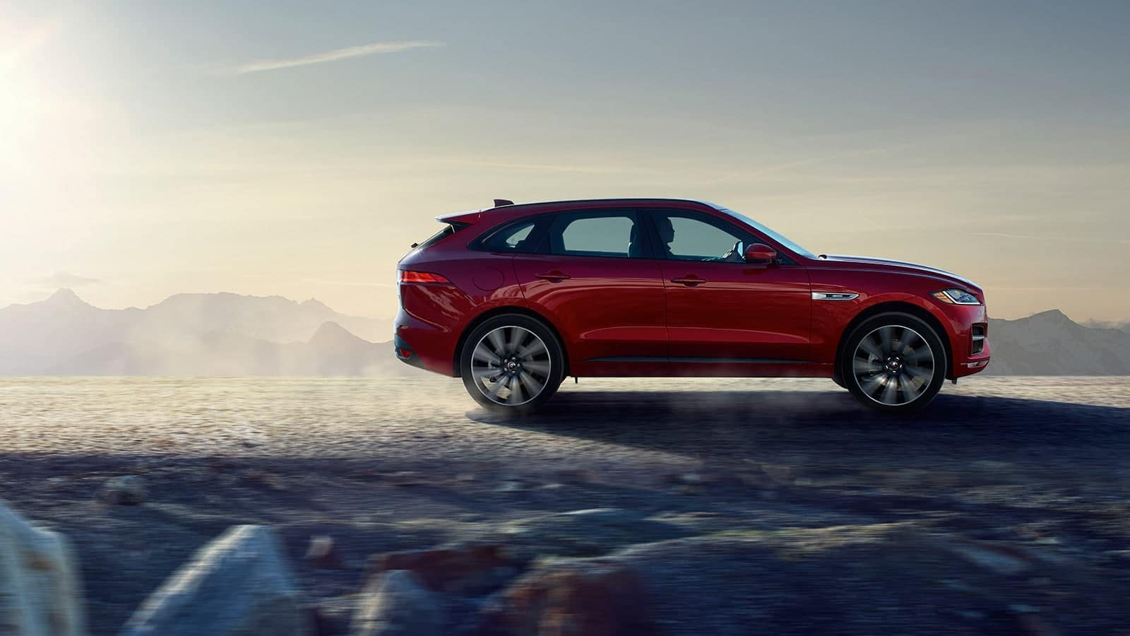 2019 Jaguar F-Pace in red driving down unpaved road