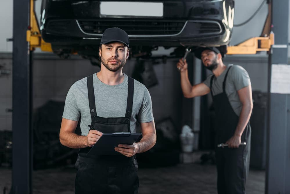 auto service technician holds clipboard for auto service