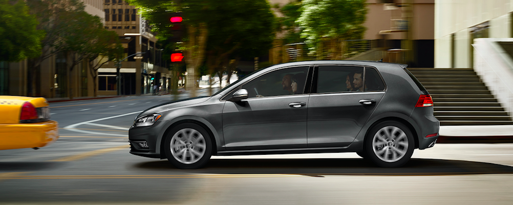 2019 Volkwagen Golf in gray driving behind a taxi