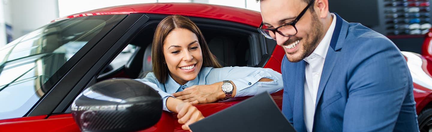 girl with agent in red car