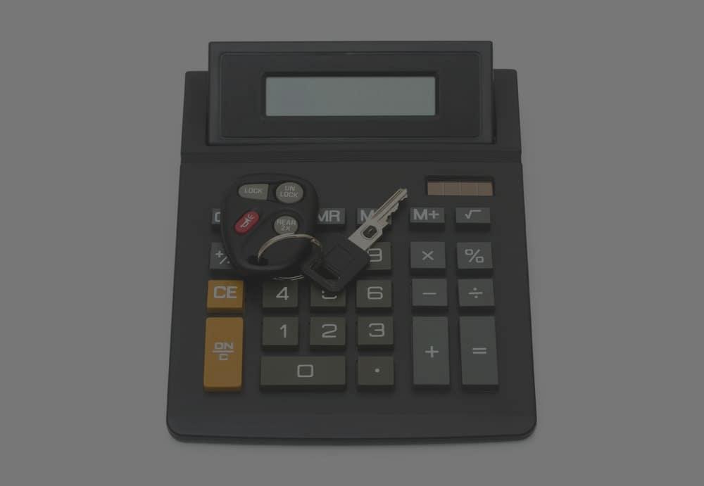 Car keys on top of a calculator