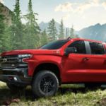 2019 Chevy Silverado 1500 in red parked in field by mountain