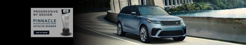 PROGRESSIVE BY DESIGN. PINNACLE RETAILER EXCELLENCE AWARD. 2019 - 2020 WINNER. FIND OUT MORE. IMAGE OF PINNACLE RETAILER EXCELLENCE AWARD. BLUE RANGE ROVER VELAR DRIVING UNDER OVERPASS NEAR LAKE.