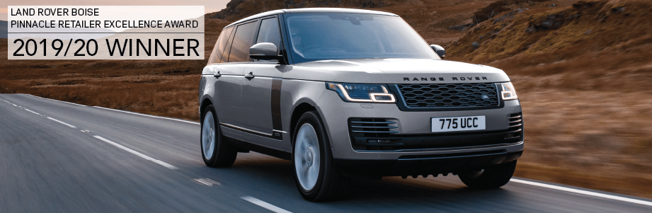 LAND ROVER BOISE. PINNACLE RETAILER EXCELLENCE AWARD. 2019/20 WINNER. GRAY RANGE ROVER SPORT DRIVING DOWN ROAD AT SUNSET.