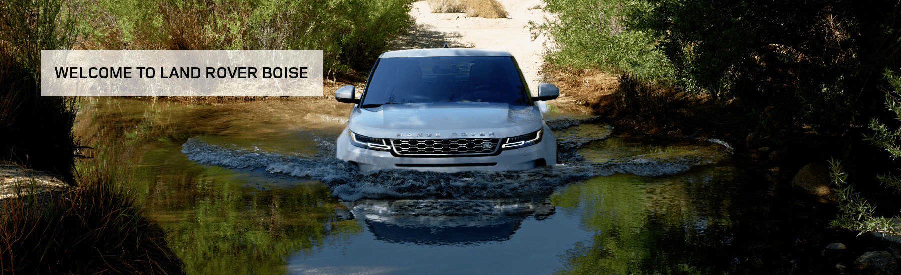 WELCOME TO LAND ROVER BOISE. WHITE RANGE ROVER EVOQUE DRIVING INTO LAKE IN FOREST.