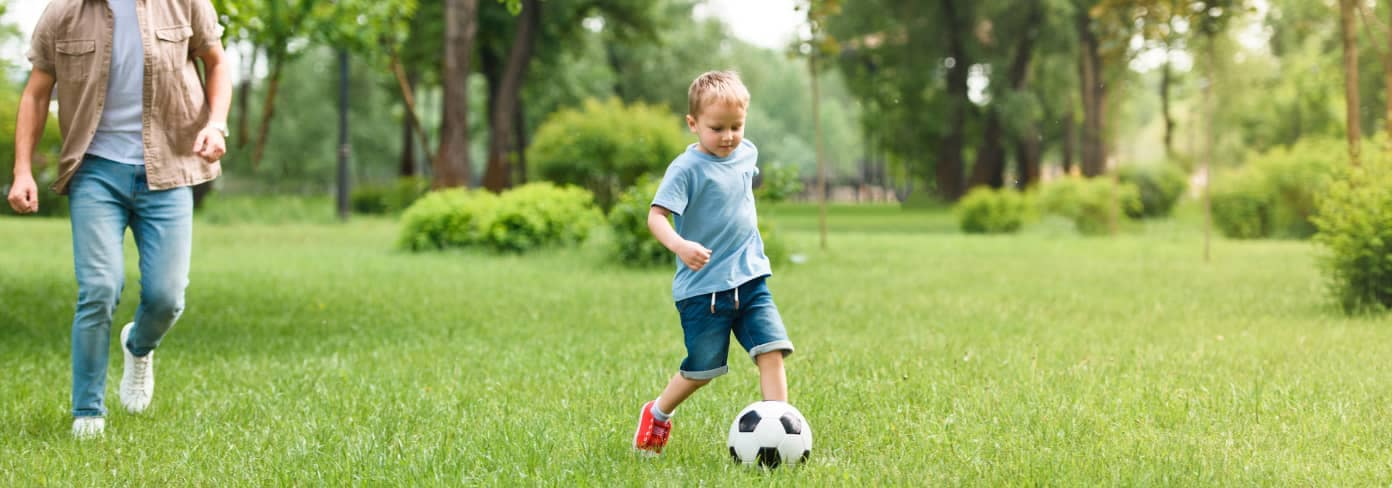 father and son play soccer in park