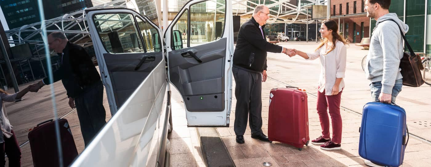 couple with luggage take hotel van