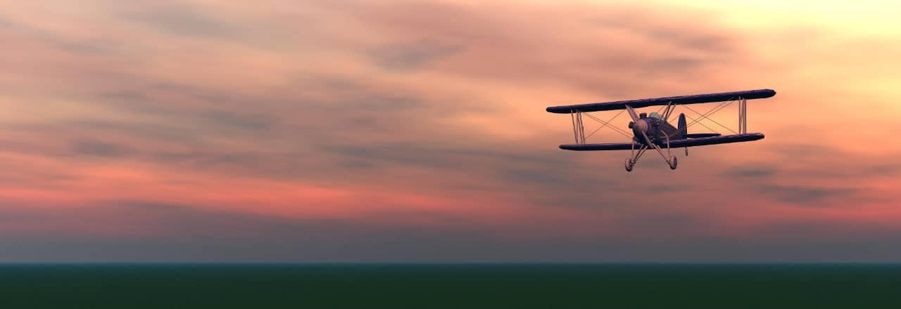 Biplane flying in sunset