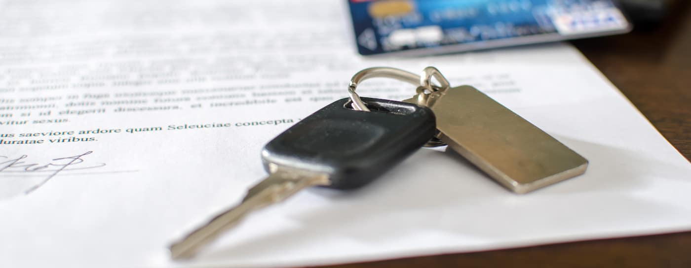 Car keys and a credit card on top of a signed car loan
