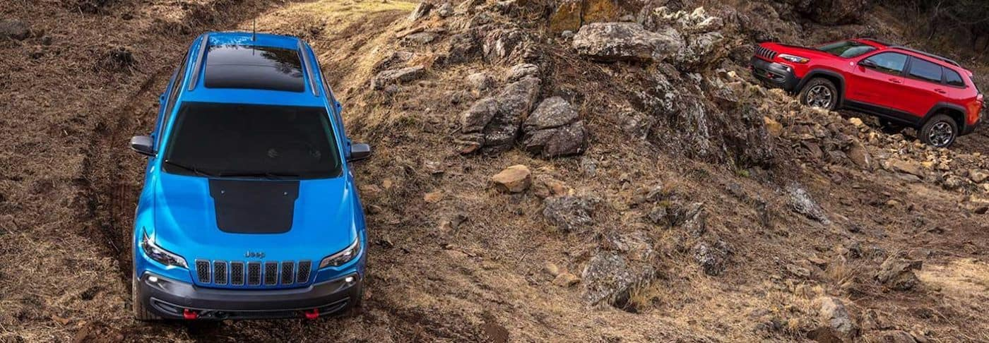 Two 2020 Jeep Cherokee models using low gear on a mountain trail