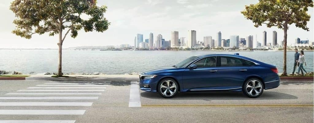 Blue 2019 Honda Accord on a city street with the ocean and a city skyline in the background
