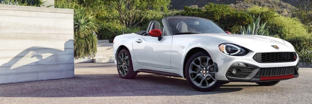 white FIAT Spider in driveway with trees in background