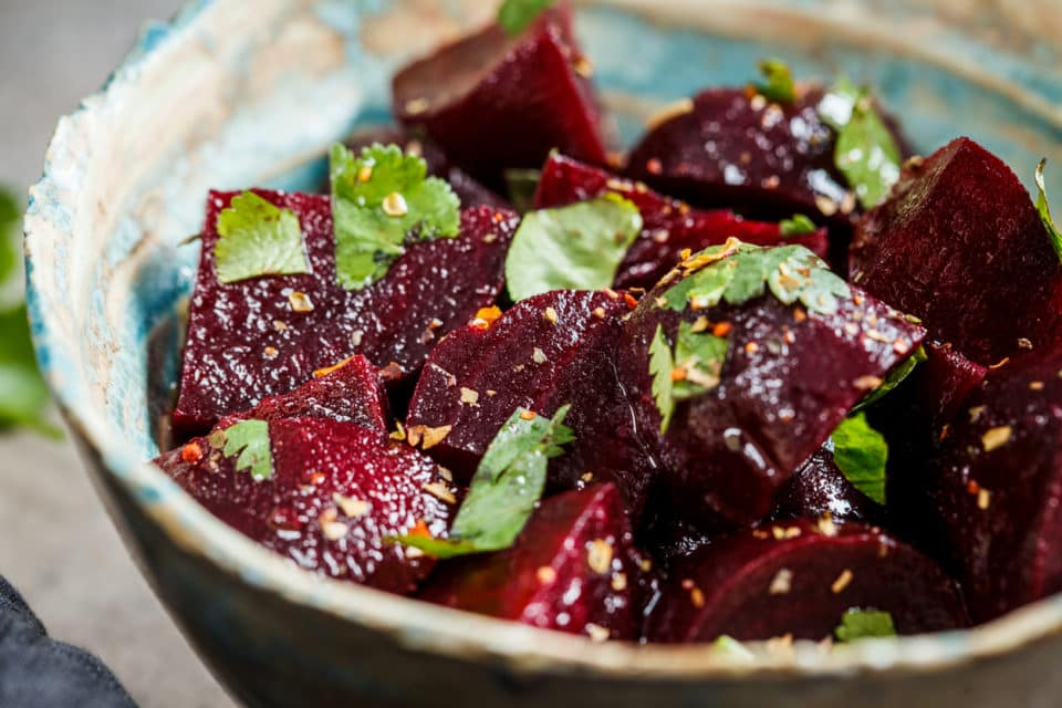 A bowl of beet salad with cilantro.