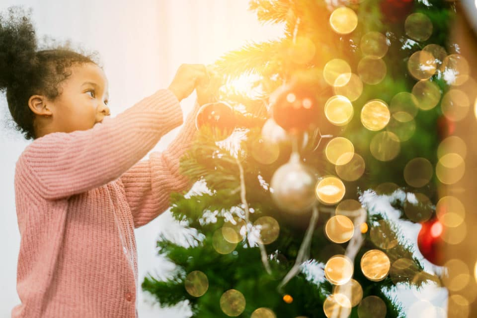 A young Black girl putting ornaments and lights on a Christmas tree.