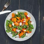 Salad with greens, sweet potato, and pomegranate seeds