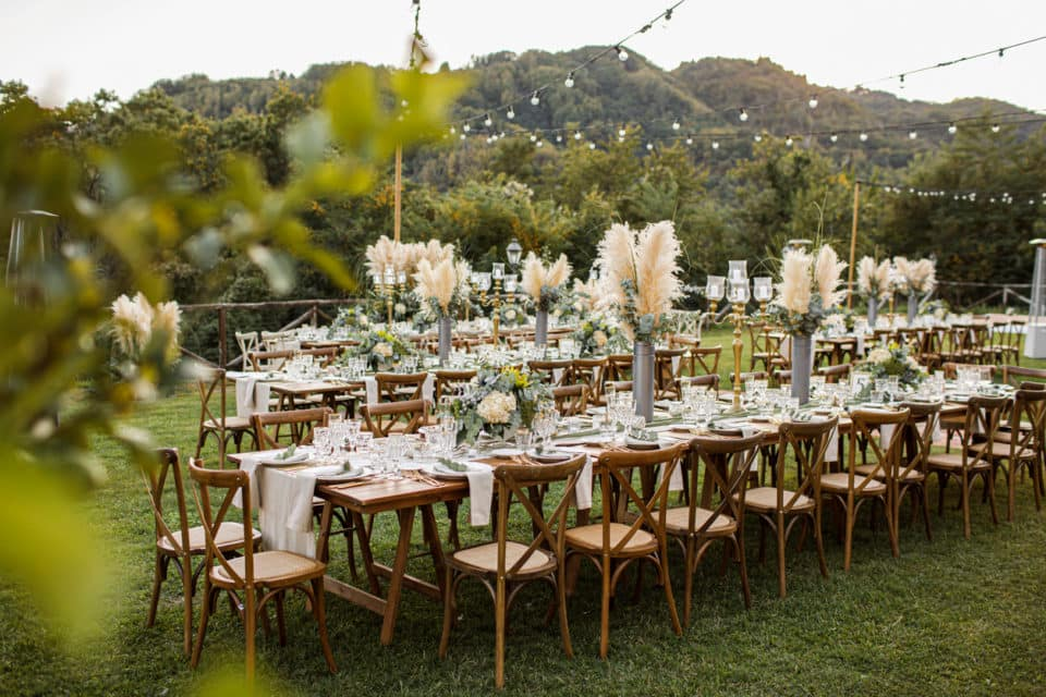 A wedding table set up in the woods. Boho vibe. Greenery, glass, pampas grass, white linens.