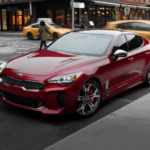 A red 2020 Kia Stinger on a city street.