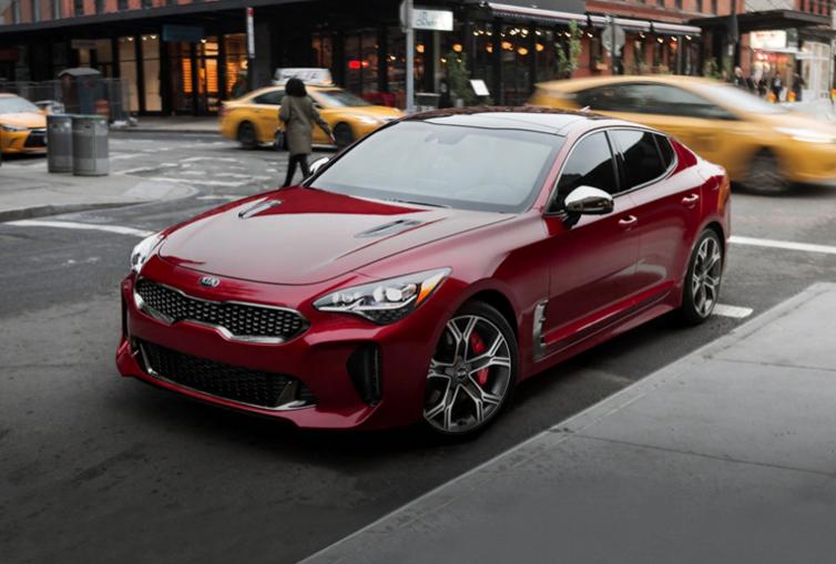 A red 2020 Kia Stinger on a city street.