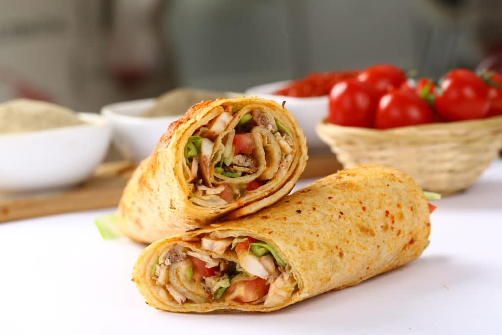 Sandwich wraps on white table with tomatoes