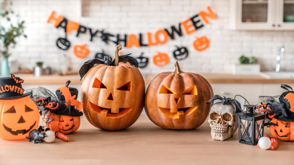 An image of two jack 'o lanterns and several other halloween decorations on a countertop. A Happy Halloween banner is in the background.