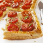 Tomato tart, puff pastry topped with mustard, cheese and cherry toamtoes.